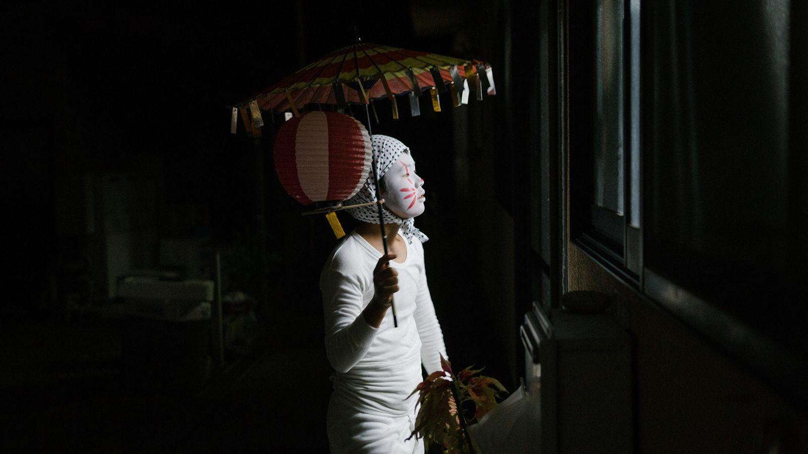 Uma criança vestida de kitsune, ou raposa, olha para dentro da casa de um vizinho durante ...