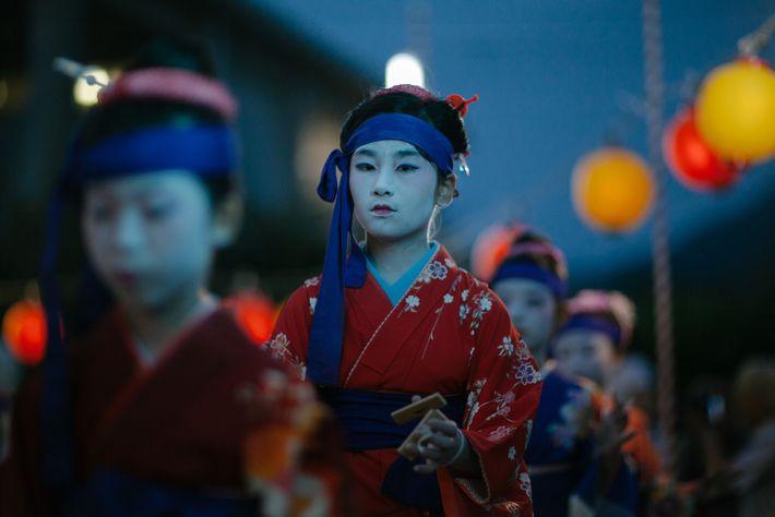 Uma menina vestida de geisha na fila no início da dança do Obon na Ilha Himeshima.