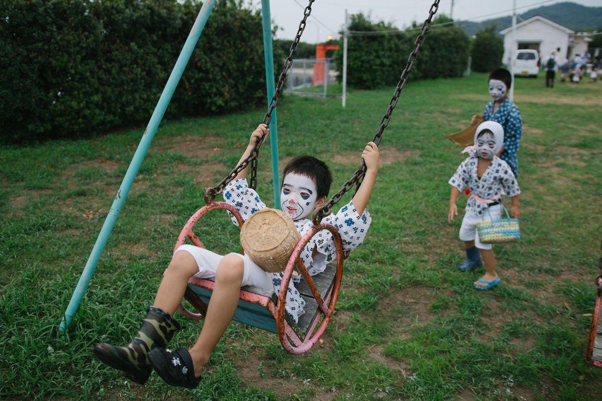"""Crianças vestidas de """"pescadores bêbados"""" brincam na rua durante o festival de Obon."""