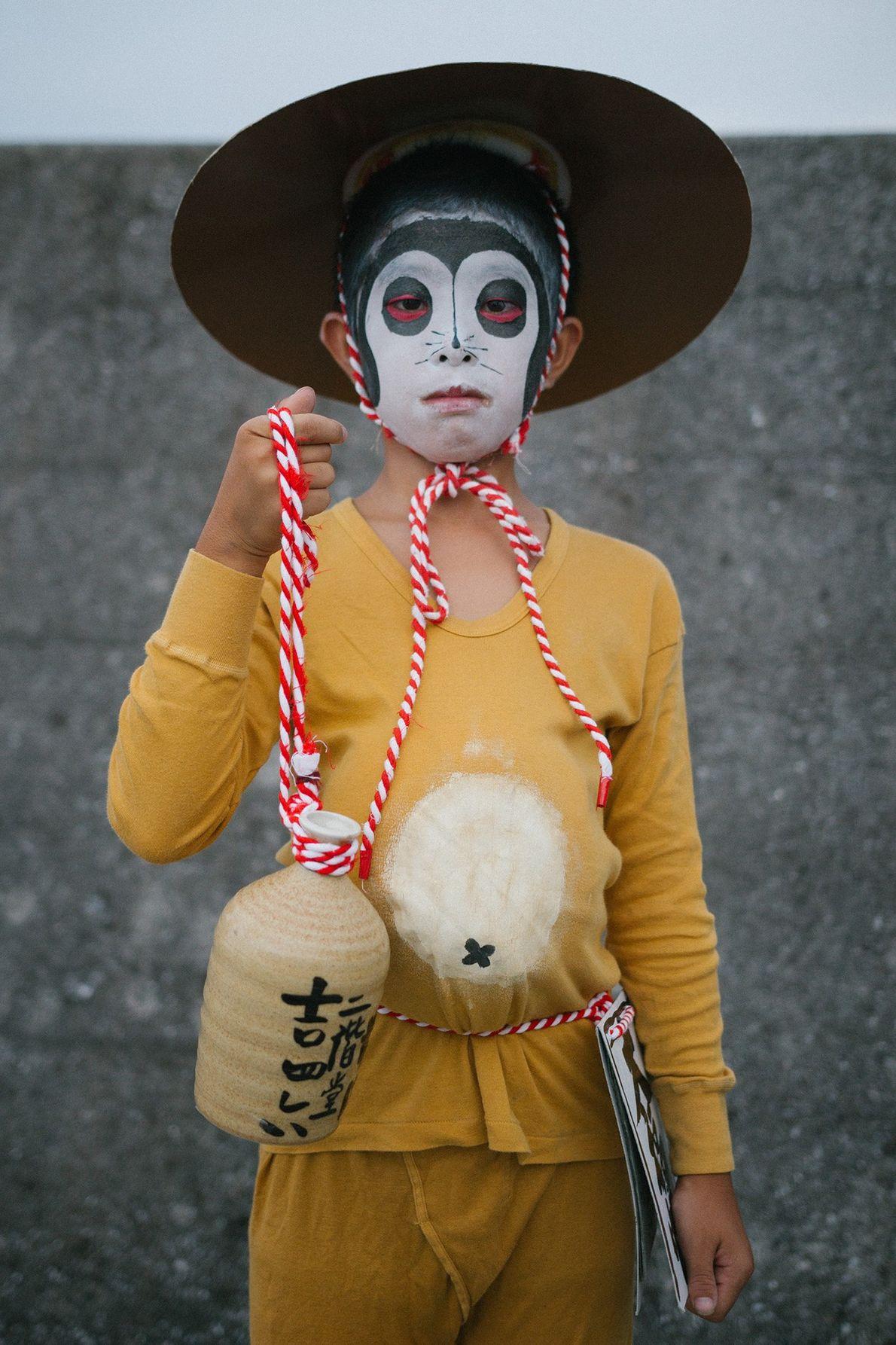Crianças vestidas de personagens populares do folclore japonês – kitsune, geisha e tanuki – posam para ...