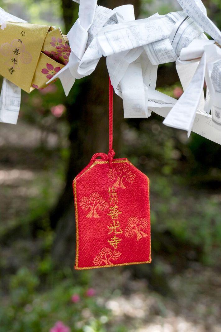 Um omamori, bolsa de seda que contém orações, pendurado perto de um templo em Nagono, Japão.