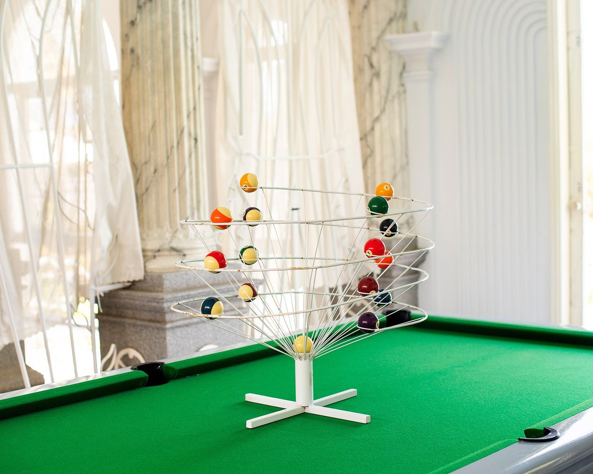Bui projetou seu próprio suporte para bolas de bilhar em formato elipsoidal. O centro imita um ...