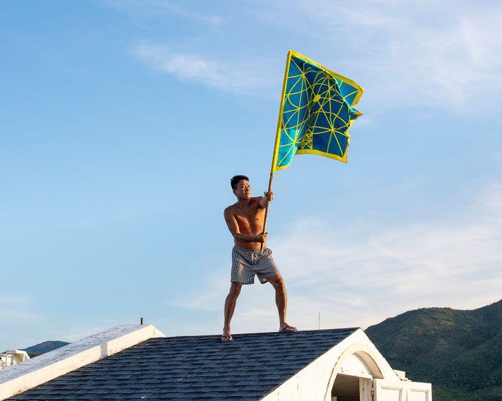 Bui no telhado agitando sua Bandeira da Paz, que ele acredita que deveria ser a bandeira ...