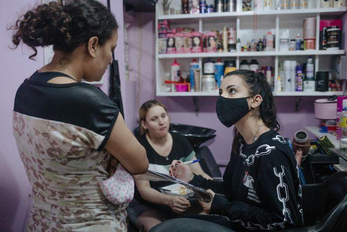 Stephany, voluntária do departamento social, faz o cadastro de famílias para receber doações de leite na favela ...