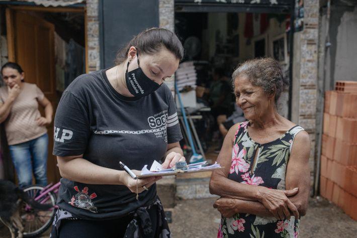 Luka, voluntária do departamento social, faz o cadastro de famílias para receber doações de leite na favela ...