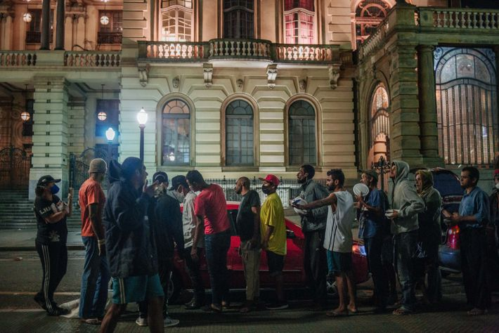 Voluntários do departamento social da torcida organizada Gaviões da Fiel distribuem marmitas na frente do Teatro ...