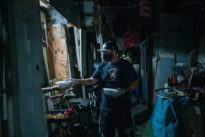 Maicon, voluntário do departamento social, entrega marmitas para moradores da Favelinha do Playcenter, no bairro Barra Funda, ...