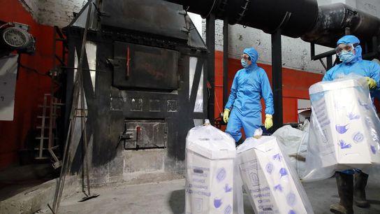 Trabalhadores em Kiev, na Ucrânia, descartam máscaras e luvas cirúrgicas usadas, queimando-as em um incinerador.