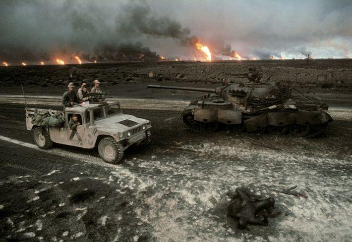 Uma patrulha dos Estados Unidos passa por um tanque iraquiano destruído e um cadáver carbonizado. As ...