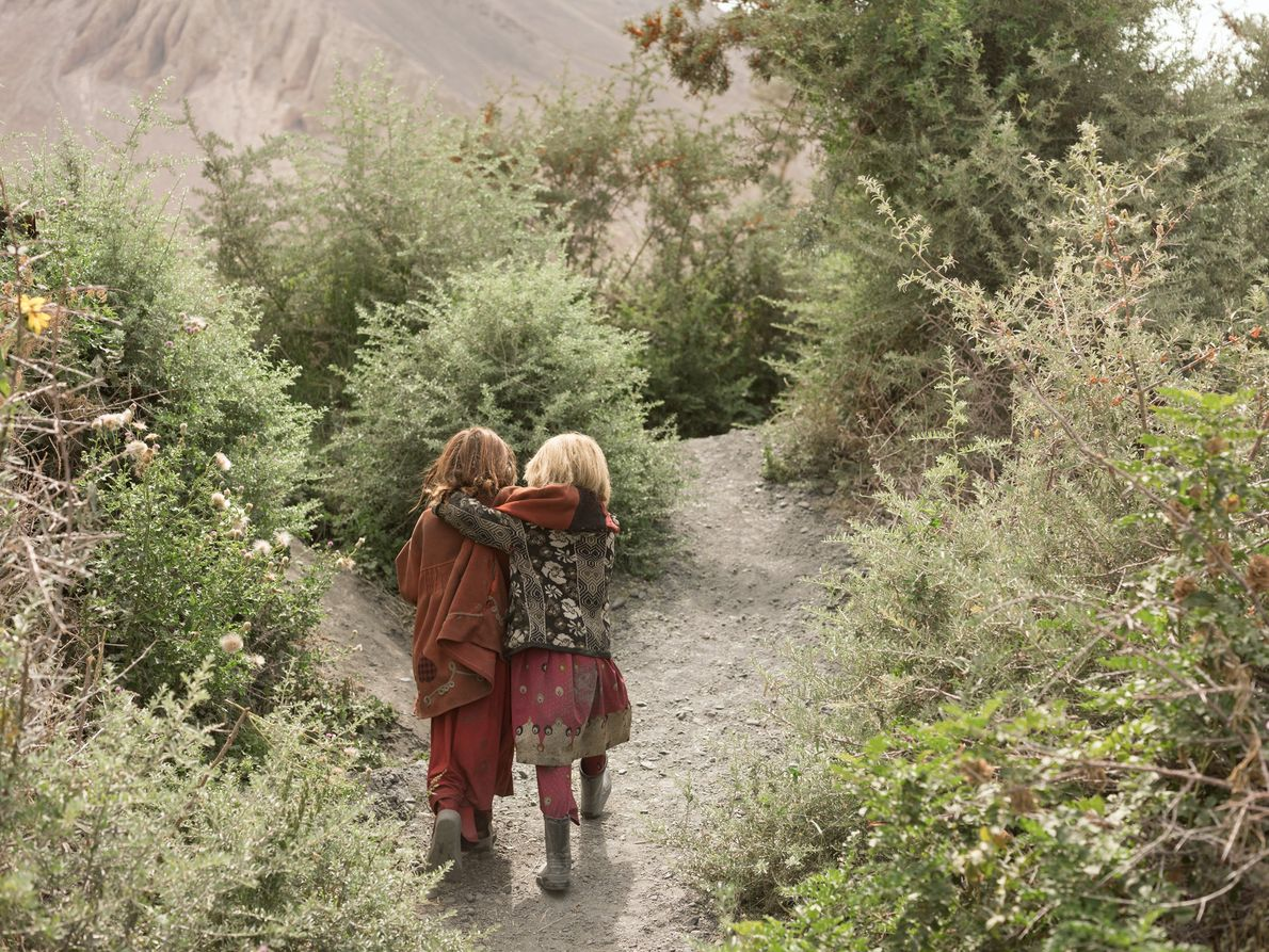 Anor Gul, 6, à esquerda, e Gul Shira, 7, seguem ao encontro de outras crianças coletando ...