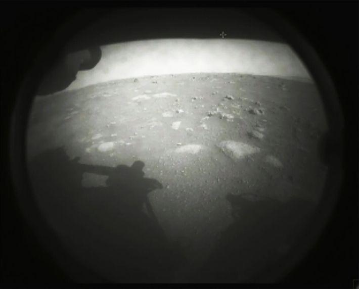O jipe-robô Perseverance tirou esta primeira foto da superfície poeirenta de Marte poucos segundos depois de ...