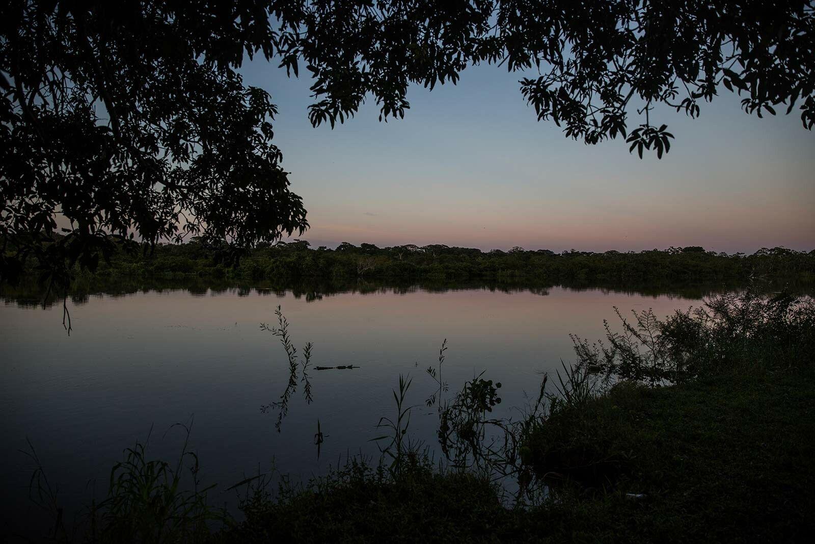 À noite o rio parece tranquilo, mas ninguém transita nele. Há pessoas armadas que vigiam o ...