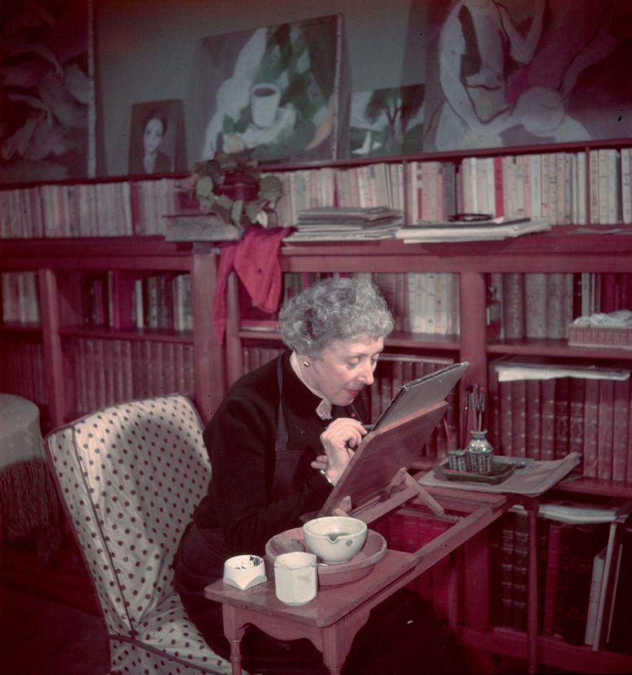 A pintora francesa Marie Laurencin trabalha sozinha no cavalete de seu estúdio.