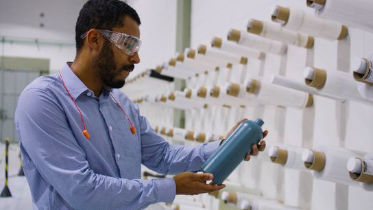 Funcionário da Dow segura protótipo de garrafa plástica produzida a partir de material reciclado.