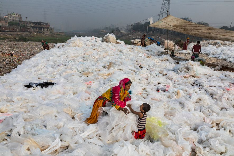 Depois da enxurrada de lixo plástico transparente ter chegado ao Rio Buriganga, em Dhaka, Bangladesh, Noorjahan estende o material para secar, virando-o regularmente, enquanto também cuida de seu filho, Momo. O plástico será vendido para um local de reciclagem. Menos de um quinto de todo o plástico é reciclado mundialmente. Nos Estados Unidos, o montante é de menos de 10%.
