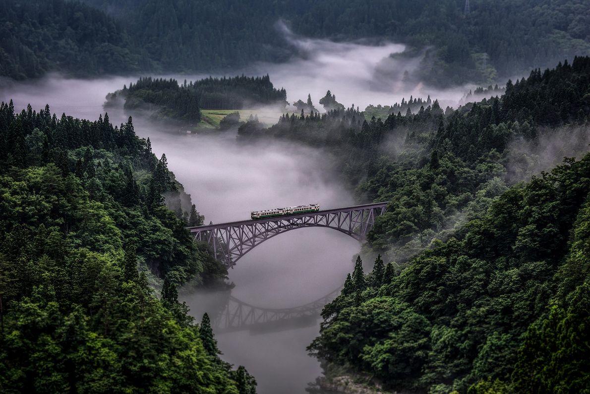Foto de uma ponte de trem no meio da neblina no Japão