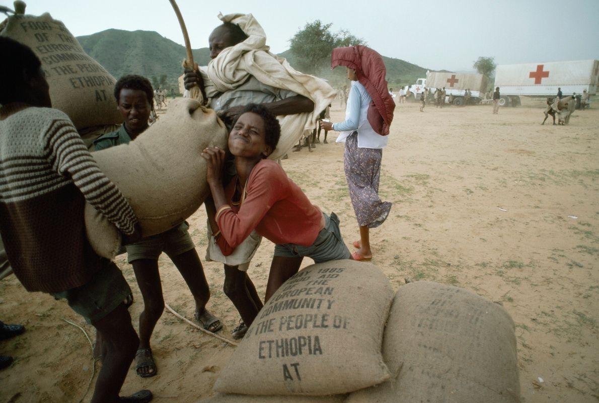Pessoas carregando sacas de grãos
