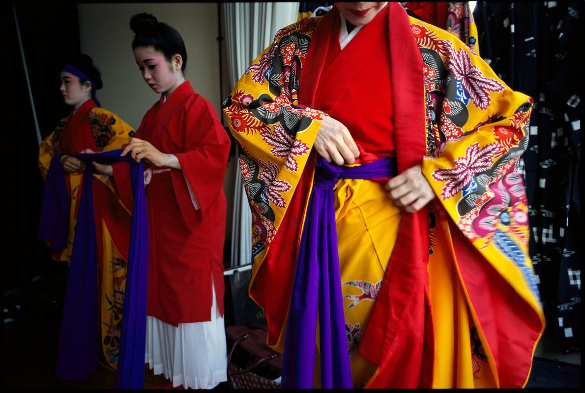 Dançarinas japonesas ajustam vestes antes de se apresentarem