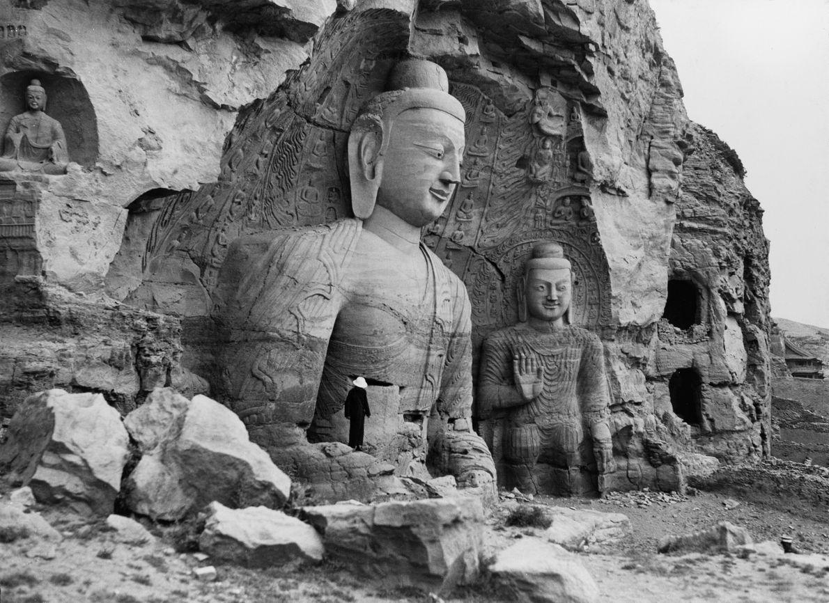 Pessoas observam estátuas gigantes de Buda