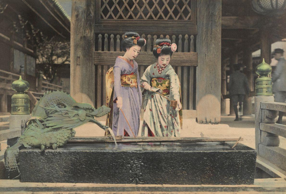 foto antiga colorida manualmente de duas mulheres japonesas em frente a templo budista