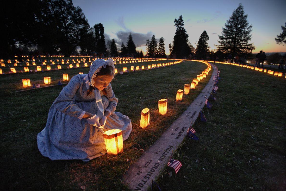 mulher em frente a velas em cemitério