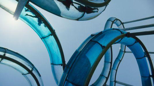 Foto de baixo para cima de tubos de tobogã azuis com pessoas dentro