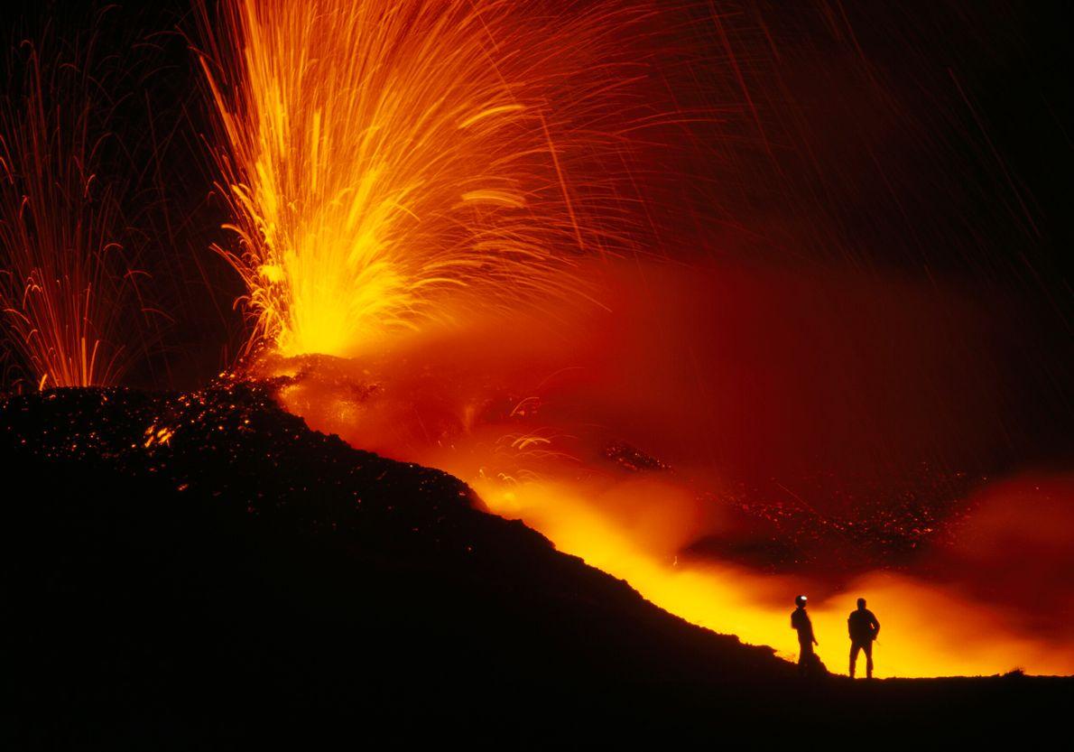 silhueta de duas pessoas em frente a vulcão em erupção
