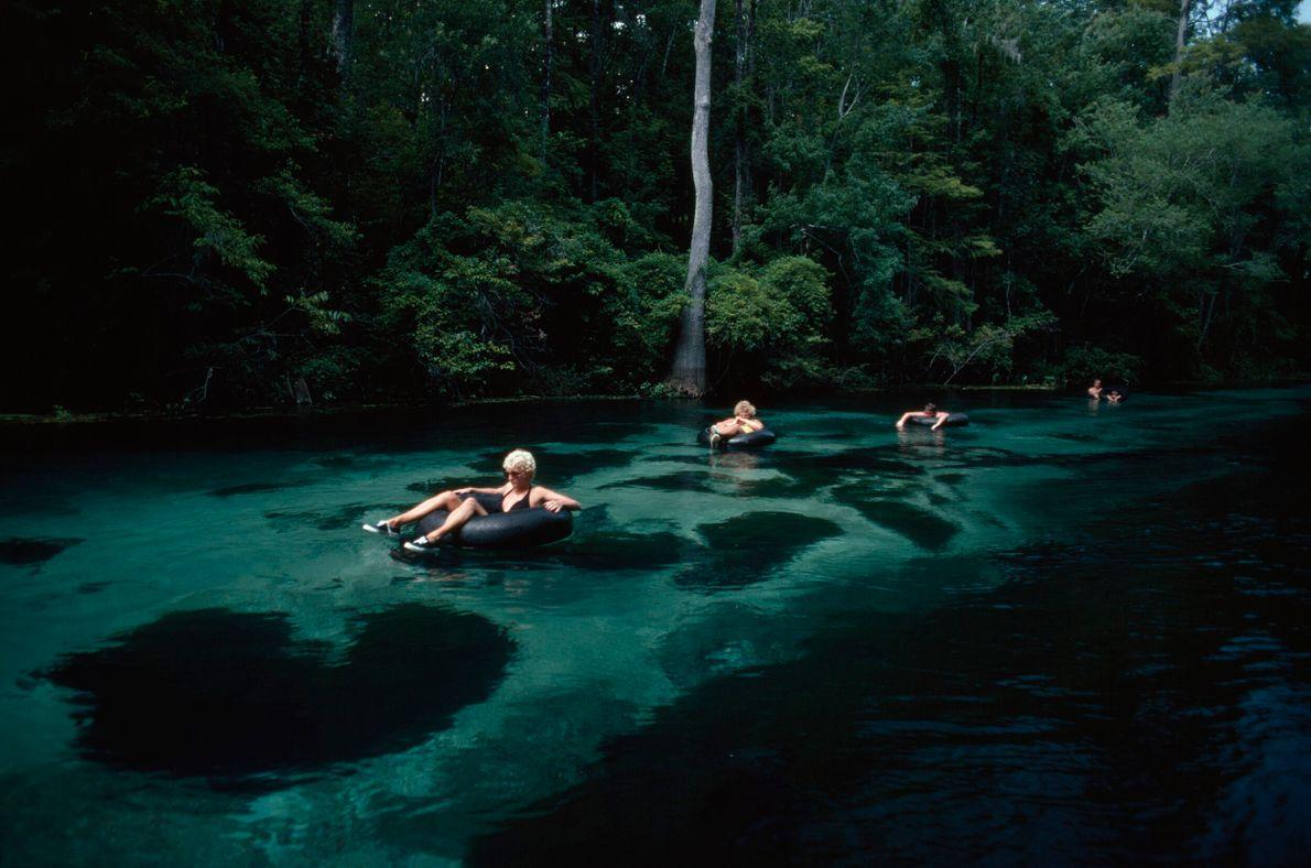 banhistas sobre boias em rio de águas verdes