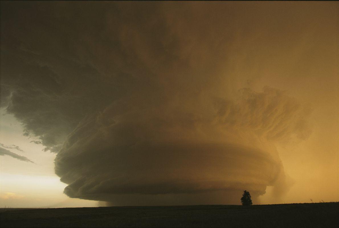 foto de uma enorme formação de nuvem e uma silhueta de casa