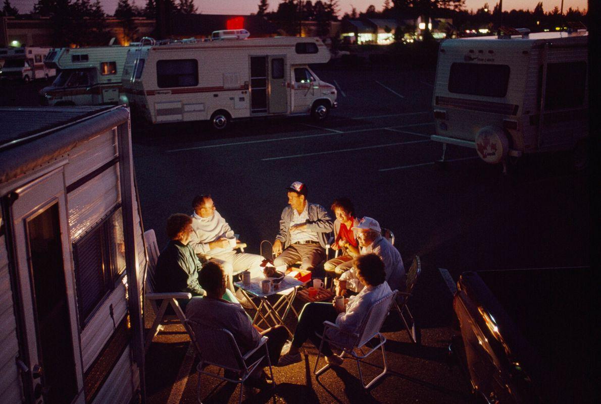 pessoas sentadas ao lado do trailer onde estão acampadas