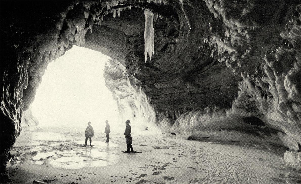 foto pb de pessoas dentro de uma caverna