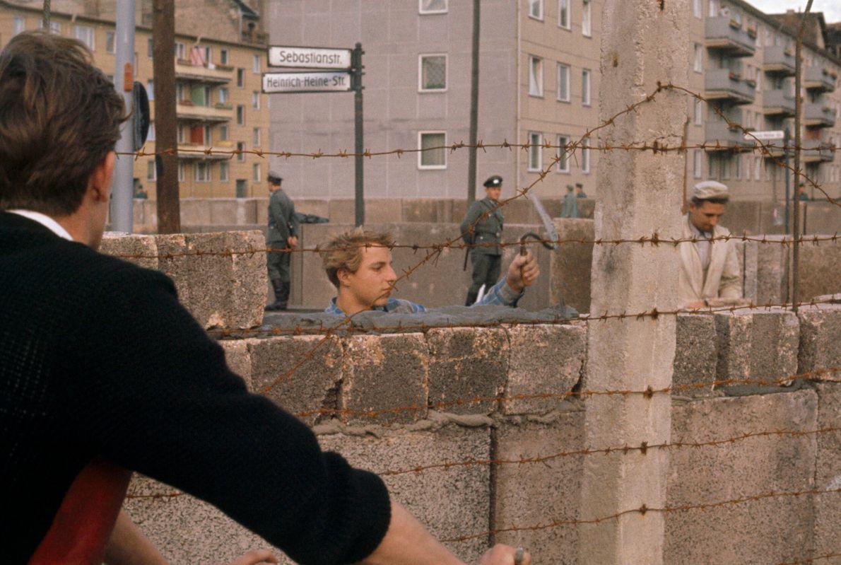 pedreiro ergue o muro de Berlim