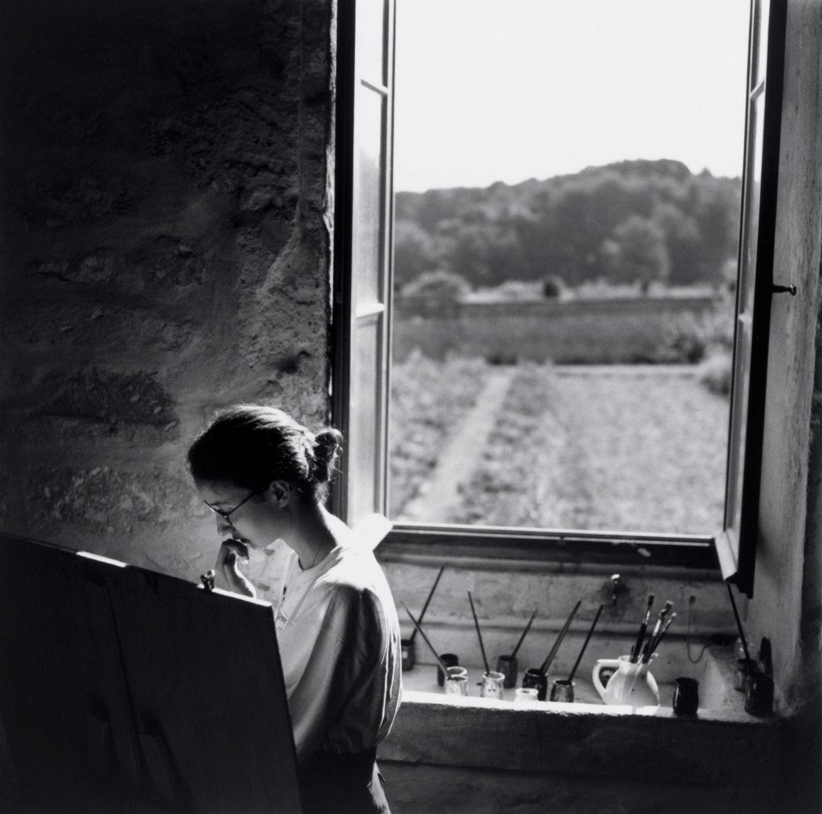 foto pb de mulher pintando um quadro a luz da janela