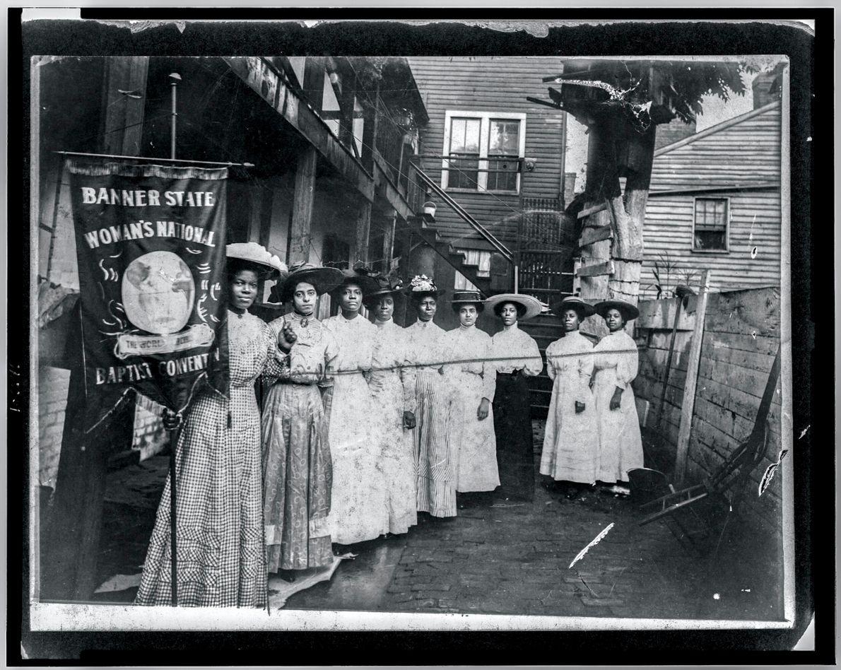 Foto pb histórica de mulheres segurando faixa de uma organização