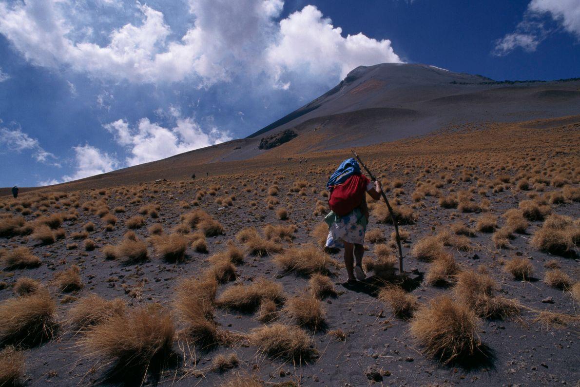 pessoa caminha em direção ao pico de um vulcão