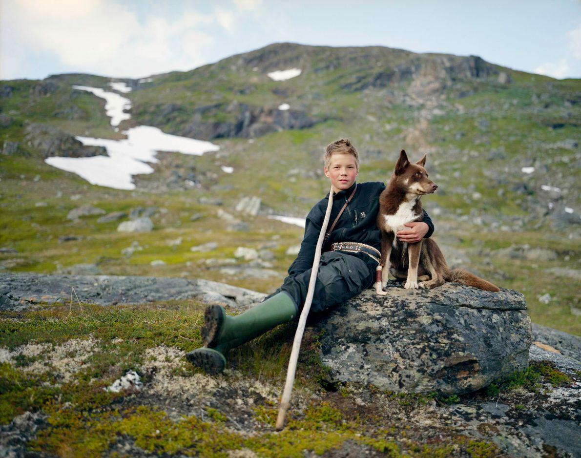 jovem garoto posando para foto ao lado de seu cachorro em um campo