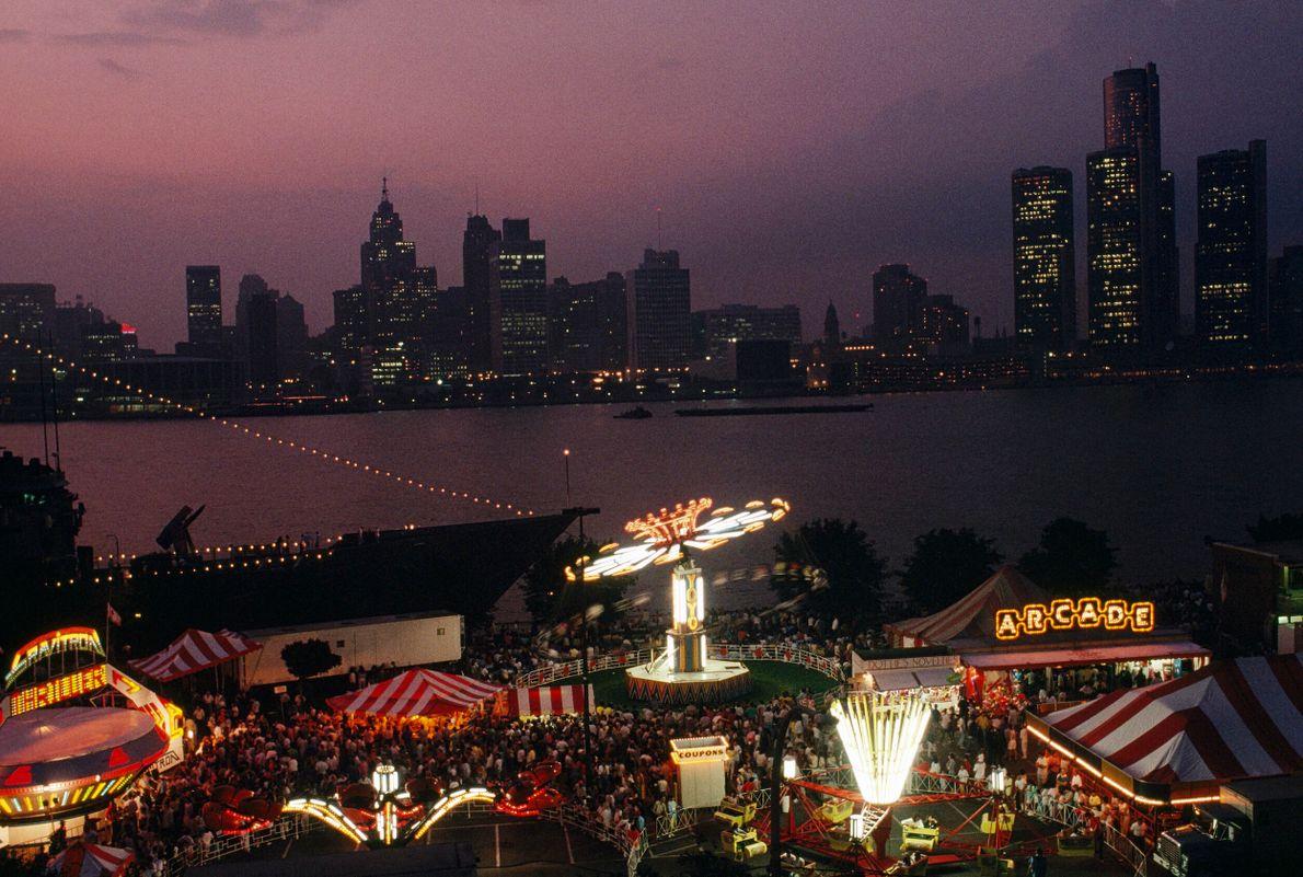 parque de diversões em primeiro plano e prédio ao fundo de noite