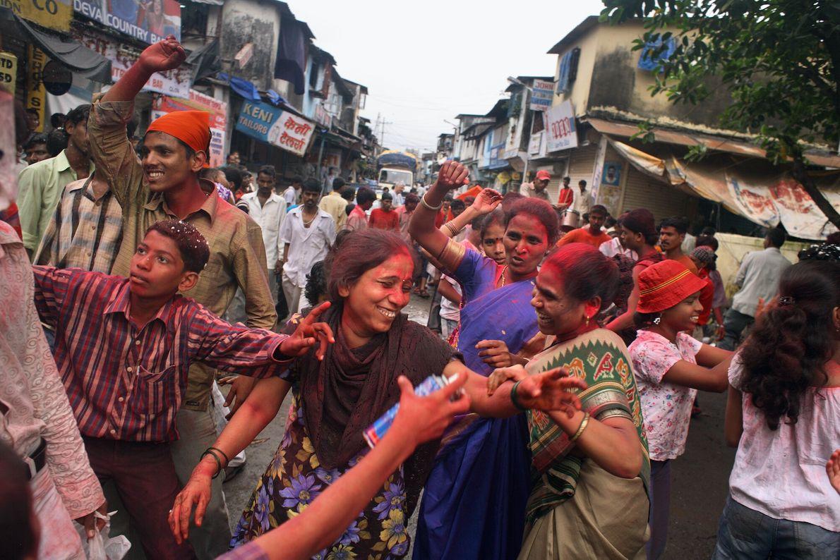 Foto de pessoas pintadas de pó colorida nas ruas em festival indiano