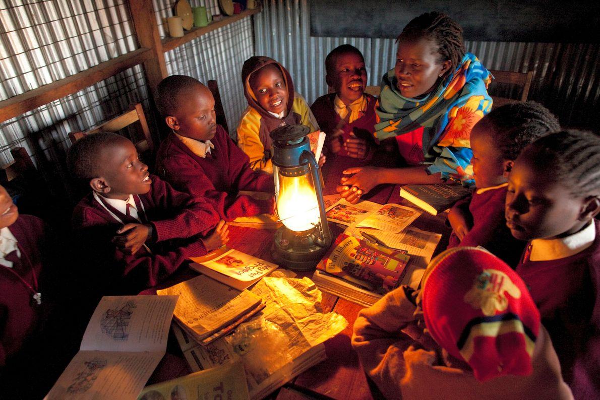 Foto de garota dando aulas a outras meninas da quarta série no Quênia, a luz de ...