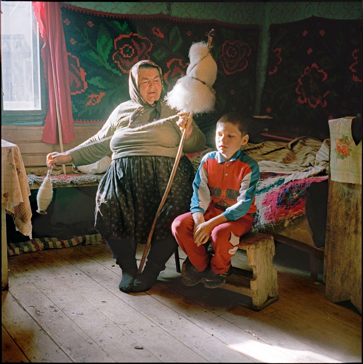 Retrato de mulher sentada fiando lã dentro de casa ao lado de criança