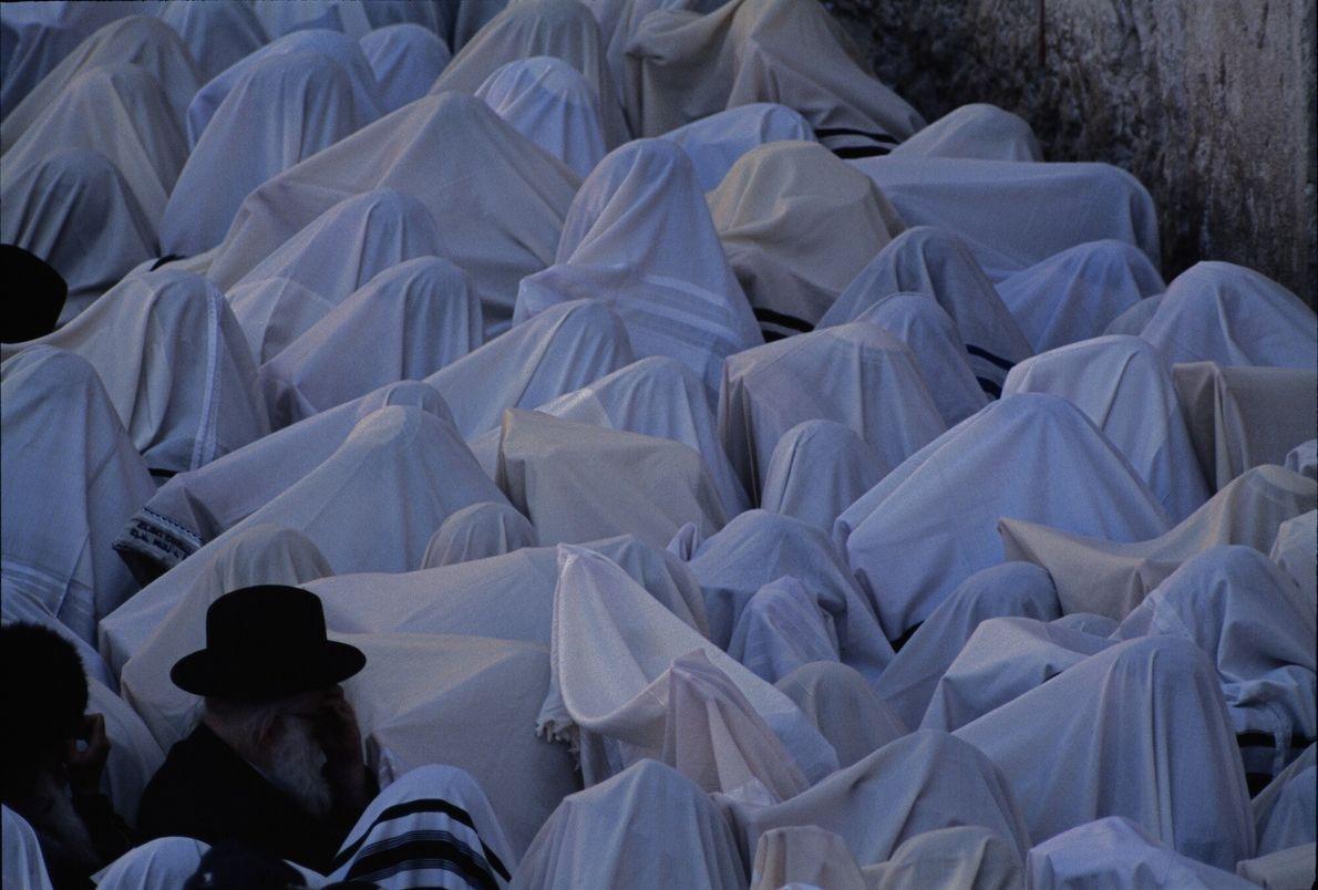 No Muro das Lamentações, xales de oração encobrem os membros de uma congregação de sacerdotes judia ...