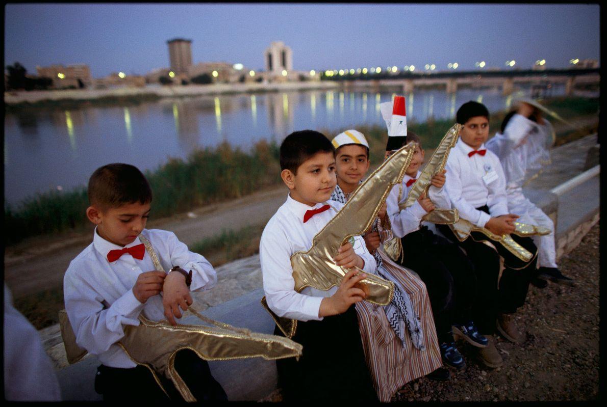 Foto de crianças segurando armas de brinquedo nas margens de um rio em Bagdad