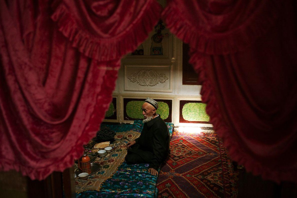 Foto de um homem sentado sobre tapetes coloridos enquanto toma chá
