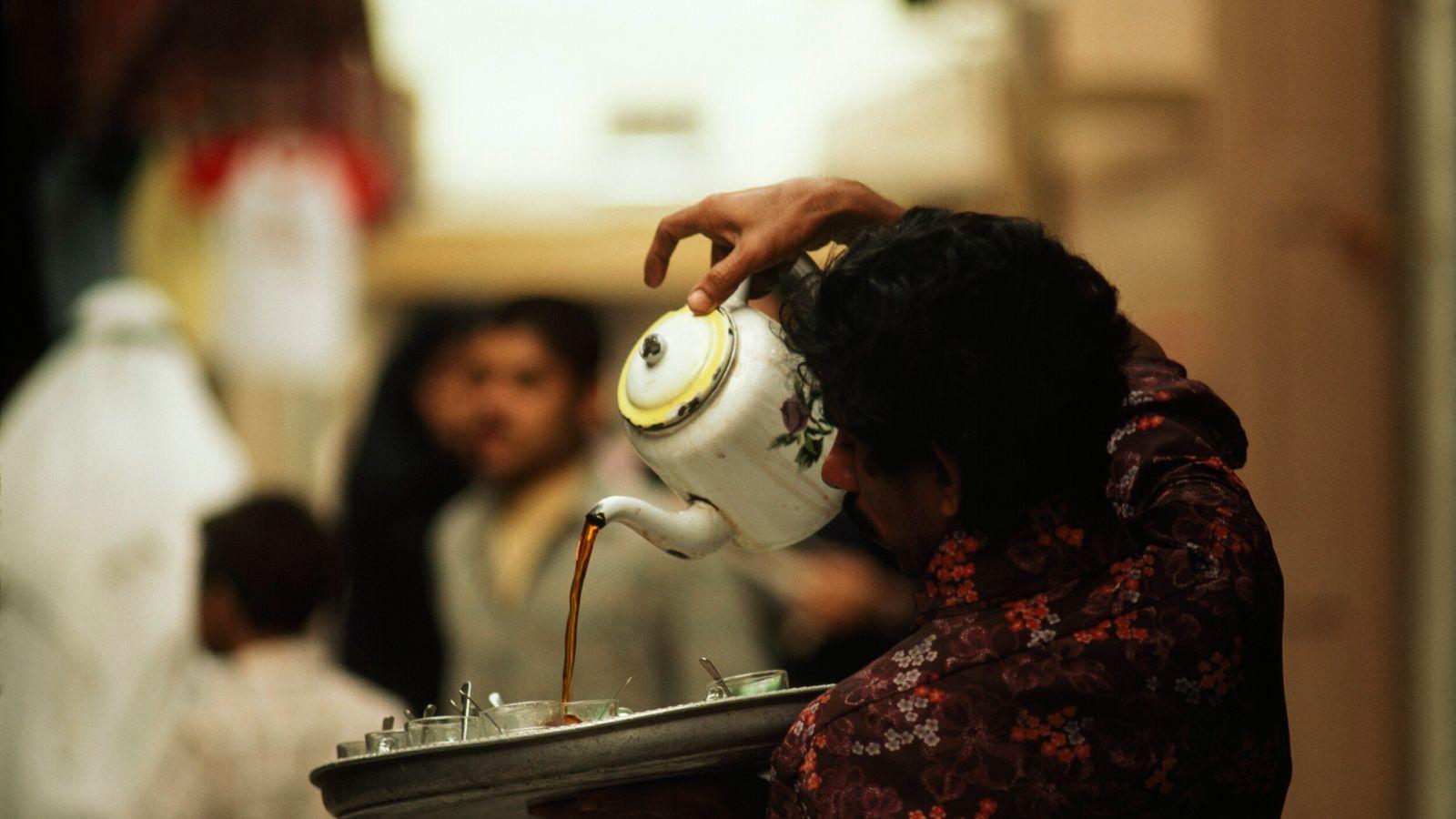 Foto de um garçom com roupa florida servindo chá a um cliente