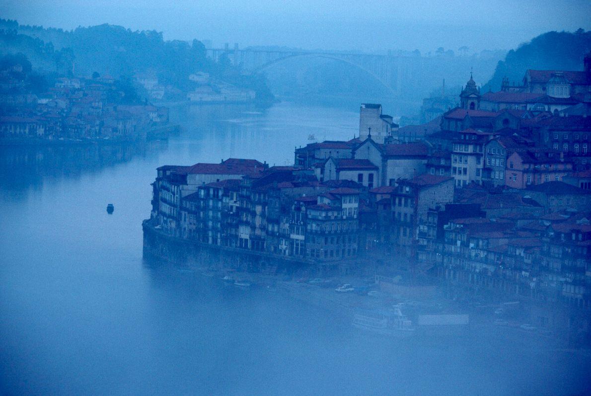 Foto azulada do rio Douro, em Porto, Portugal, embaixo de uma névoa com uma ponte ao ...