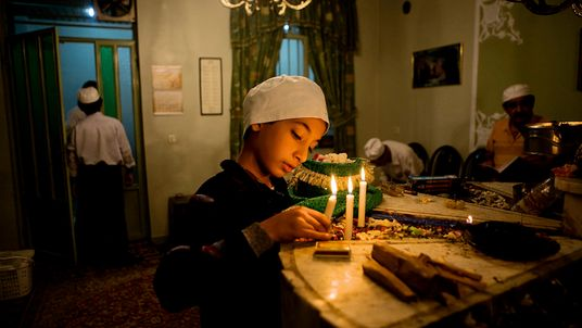 Fot de um garoto iraniano vestindo um gorro branco e acendendo uma vela no festival persa ...
