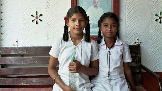 foto de duas estudantes em frente a um retrato de Gandhi em uma escola fundada por ...