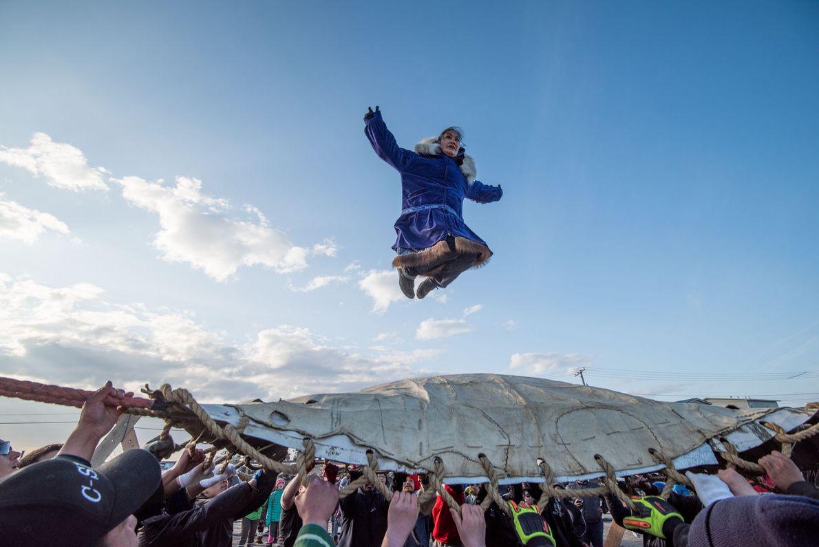 No Nalukataq, o festival de pesca de baleias de Utqiaġvik, pessoas celebram uma produtiva temporada de ...