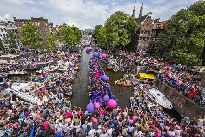 Cerca de 80 barcos com participantes animados flutuam pelo famoso sistema de canais de Amsterdã.