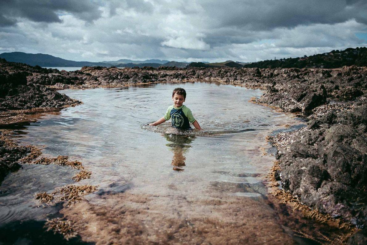 Menino andando pela água em uma praia da Nova Zelândia.